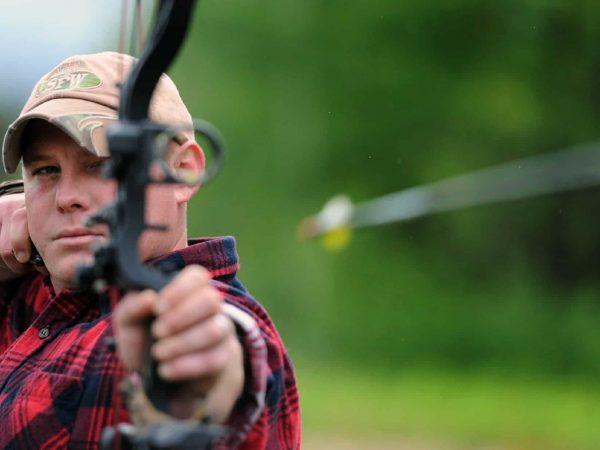 Mann schießt mit einem Bogen einen Fiberglaspfeil ab